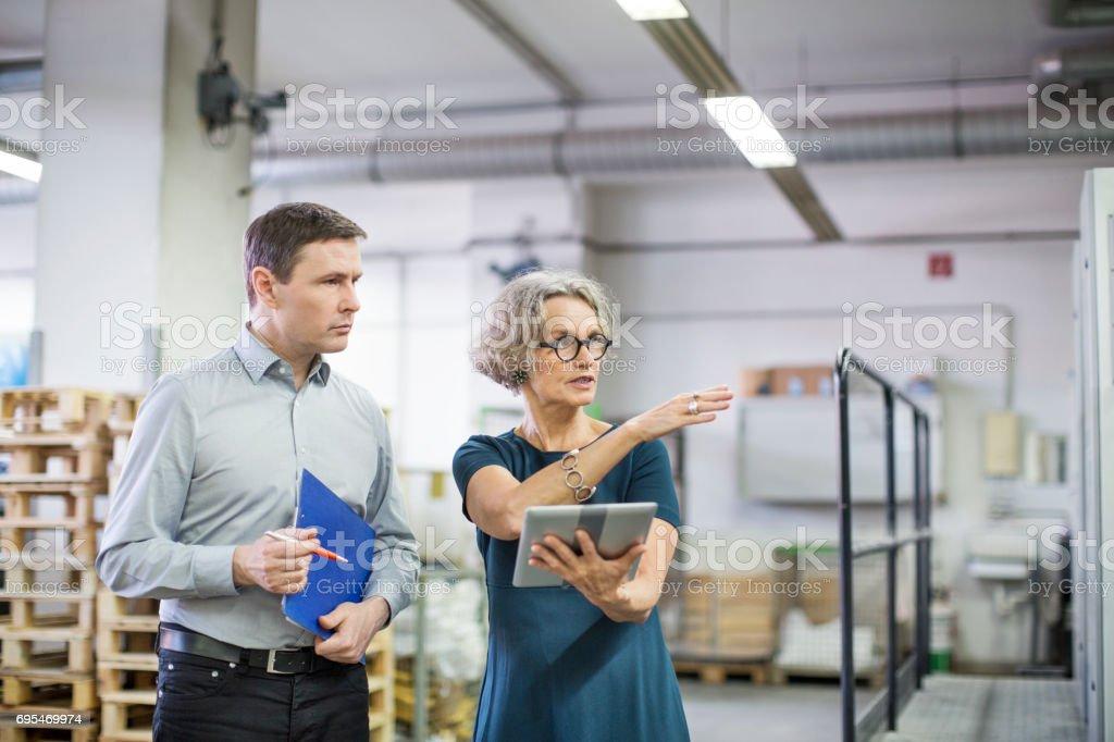 Gerente con trabajador de sexo masculino en la planta de impresión - foto de stock