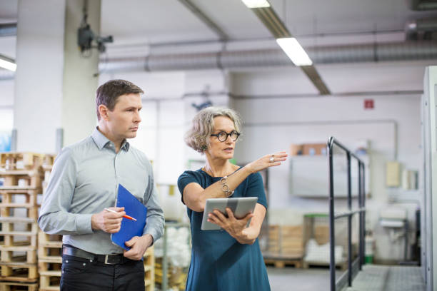 Manager discussing with male worker at printing plant stock photo
