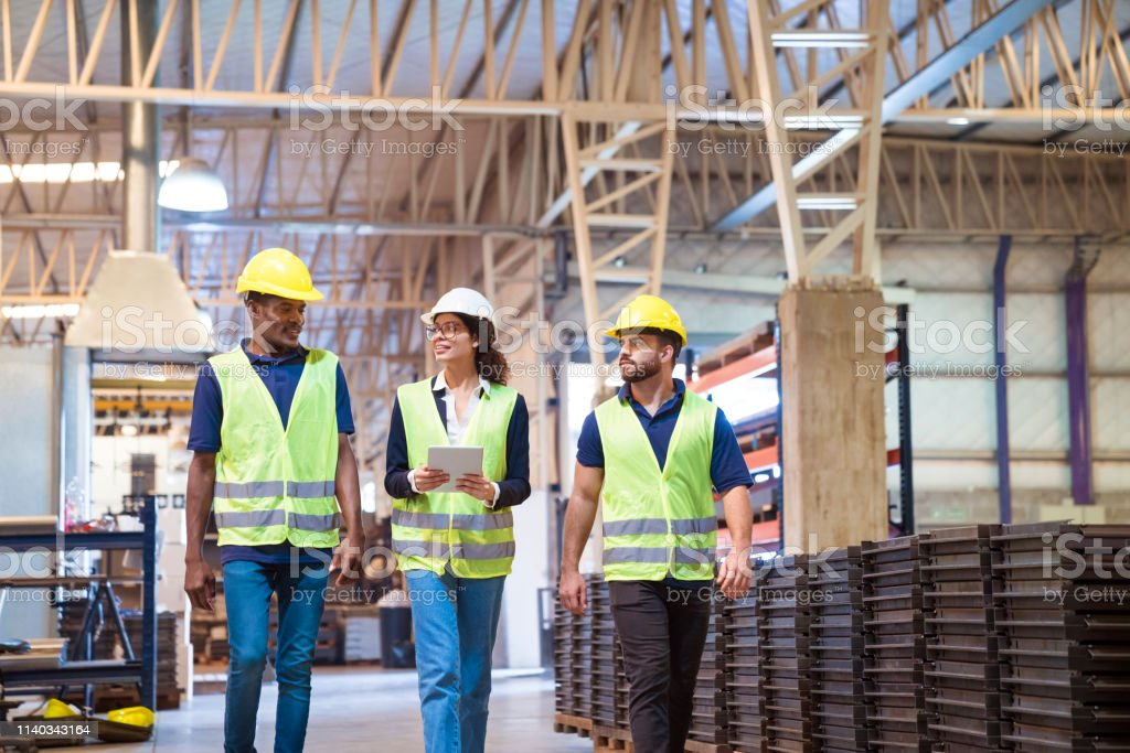 Manager discussing with trainees in factory Manager discussing with workers while holding digital tablet. Expertise are planning together in manufacturing company. They are walking in factory. 20-24 Years Stock Photo
