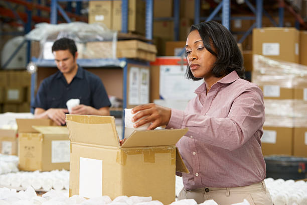 Manager does quality control on assembly line package Female Manager Checking Goods On Production Line production line stock pictures, royalty-free photos & images