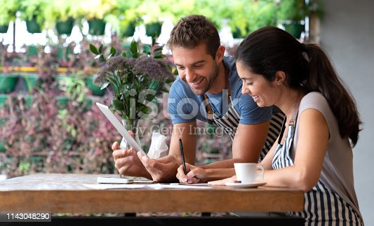 Happy manager doing the books at a restaurant with help of a waiter - small business concepts