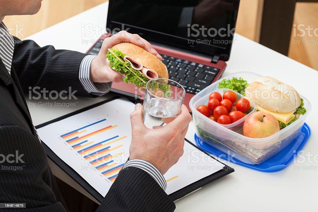Gerente de comer un sándwich en el trabajo foto de stock libre de derechos