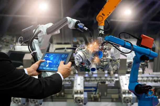 Manager engineer touch screen control automation robot arms the production of factory parts engine manufacturing industry robots and mechanical arm stock photo