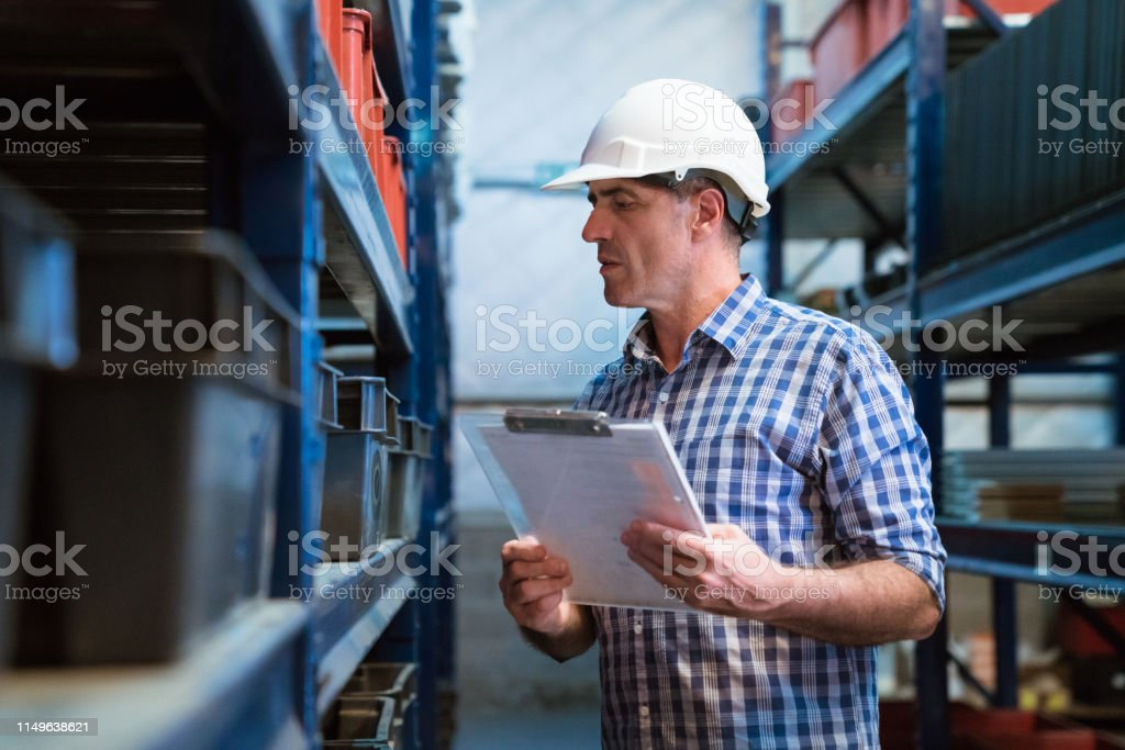 Manager examining goods in storage room Manager with clipboard examining goods in storage room. Foreman is working in distribution warehouse. He is wearing hardhat and checked patterned shirt. 55-59 Years Stock Photo