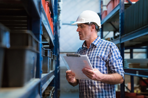 Manager Examining Goods In Storage Room Stock Photo - Download Image Now