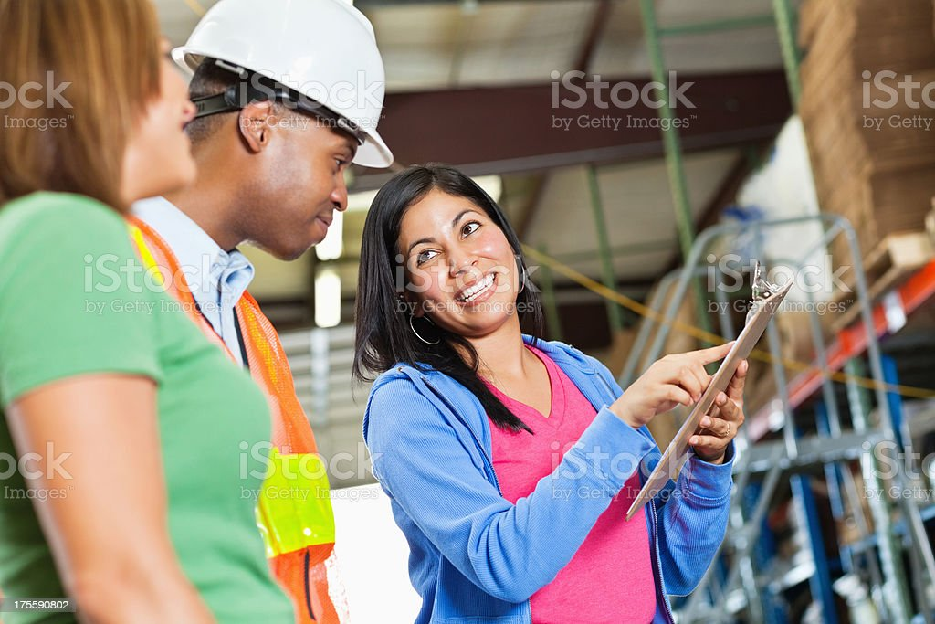Manager going over inventory with workers in a warehouse stock photo
