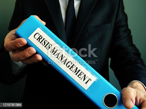 694587746 istock photo Manager holds crisis management plan in the blue folder. 1215761364