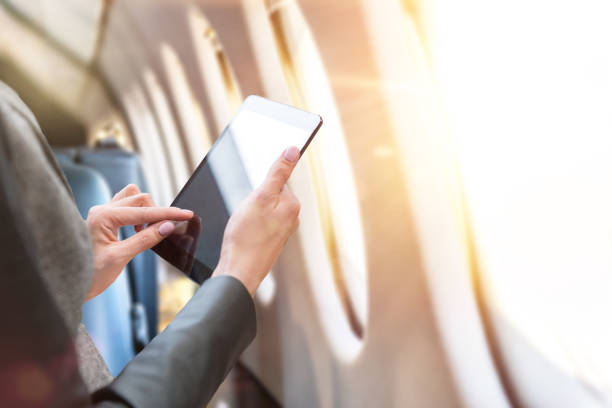 Manager in first class Horizontal color close-up image of a businesswoman with tablet in luxury airplane. Windows with sunbeams in a row. Interior of private jet. touchpad stock pictures, royalty-free photos & images
