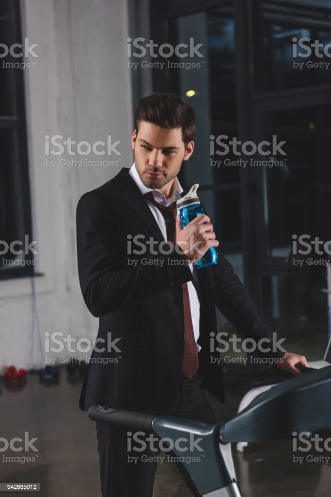 d4f80d514be1 Manager in suit training on treadmill with sport bottle in gym - Stock  image .
