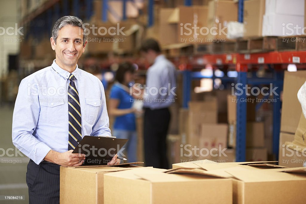 Manager In Warehouse Checking Boxes Manager In Warehouse Checking Boxes  Smiling To Camera 20-29 Years Stock Photo