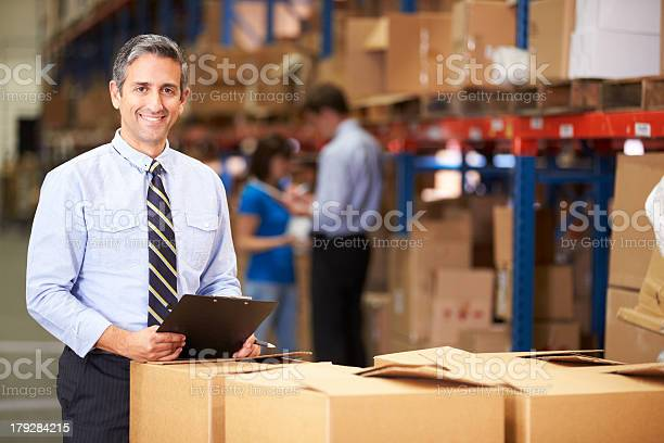 Manager In Warehouse Checking Boxes Stock Photo - Download Image Now