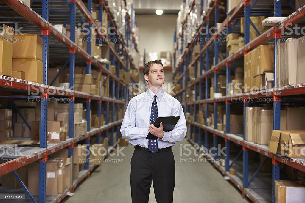 Manager In Warehouse With Clipboard Manager In Warehouse With Clipboard Looking Up At Boxes 20-29 Years Stock Photo