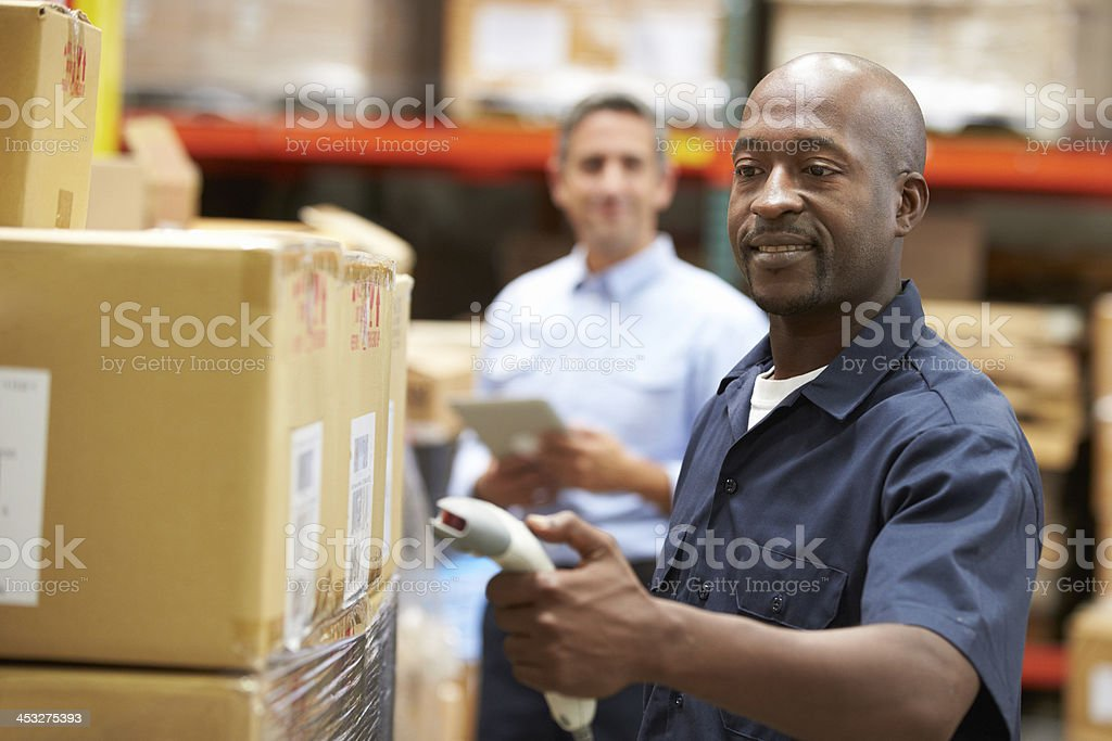 Manager In Warehouse With Worker Scanning Box stock photo