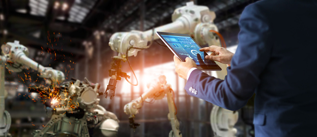 istock Manager industrial engineer using tablet check and control automation robot arms machine in intelligent factory industrial on monitoring system software. Welding robotics and digital manufacturing operation. Industry 4.0 concept. 1022855276
