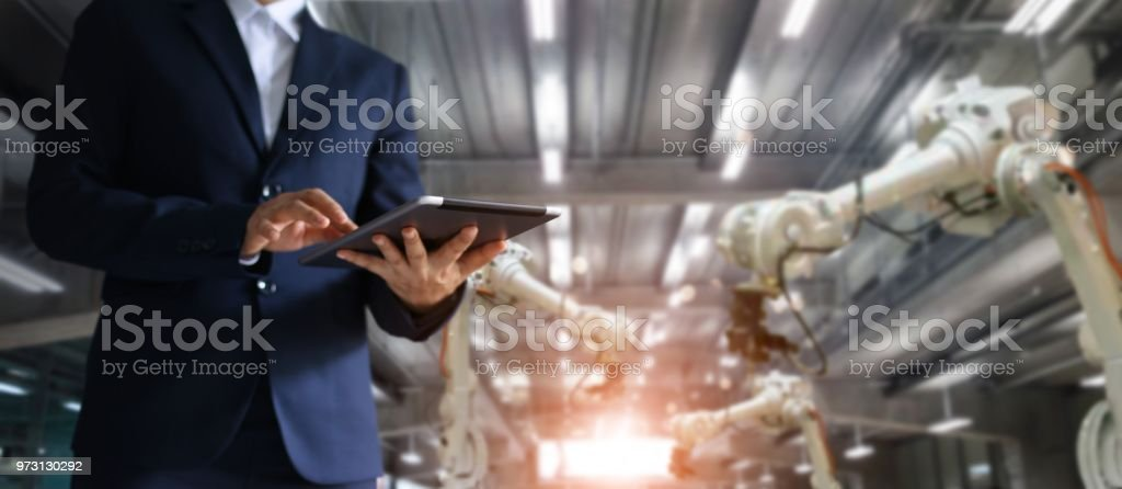 Manager industrial engineer using tablet check and control automation...