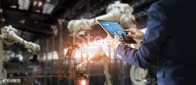 istock Manager industrial engineer using tablet check and control automation robot arms machine in intelligent factory industrial on real time monitoring system software. Welding robotics and digital manufacturing operation. Industry 4.0 concept 973143870