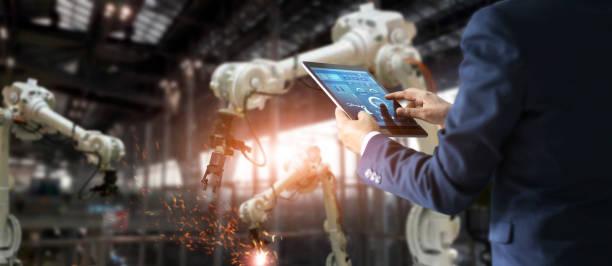 gerente ingeniero industrial usando tableta de comprobación y control maquina de brazos de robot de automatizacion industrial fábrica inteligente en tiempo real, software de sistema de monitoreo. soldadura robótica y operación de fabricación digital.  - robot fotografías e imágenes de stock