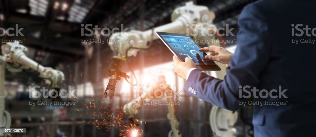 Manager industrial engineer using tablet check and control automation robot arms machine in intelligent factory industrial on real time monitoring system software. Welding robotics and digital manufacturing operation. Industry 4.0 concept stock photo