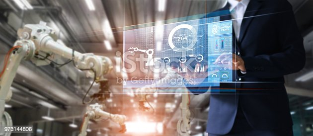 istock Manager industrial Engineer using tablet check and control automation robot arms machine in intelligent factory industrial over system on virtual interface screen, Industry 4.0 concept 973144806