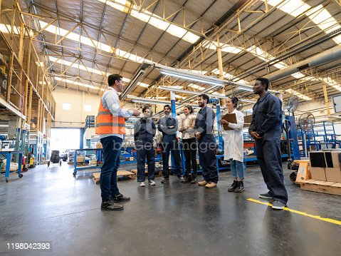 Manager instructing a diverse team of engineers, blue collar workers and quality inspectors at a factory - Manufacturing concepts