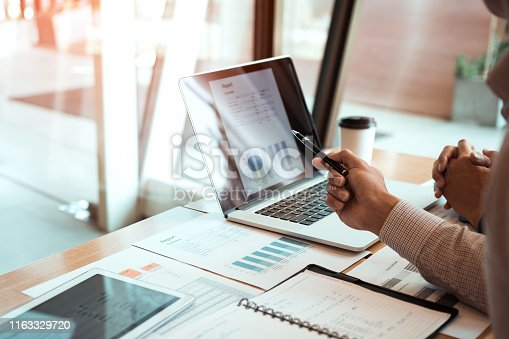 Manager is using a laptop computer while analyzing the company's financial statements on the screen.