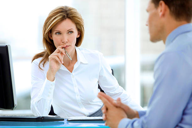 Manager listening to businessman Beautiful female manager listening to businessman at workplace persuasion stock pictures, royalty-free photos & images