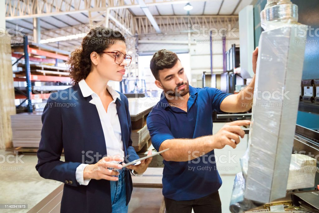 Manager looking at production worker using machine Female manager looking at production worker using machine. Expertise are working in manufacturing company. They are at factory. 20-24 Years Stock Photo
