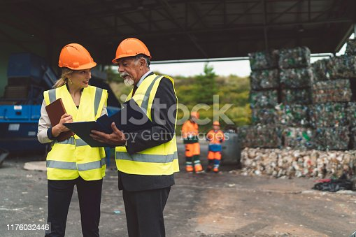 Senior man, manager at recycling facility taking to woman sanitary inspector. Wearing neon vests and protective helmet, while beeing outside the facility, examining the waste treatment. Manager holding a note pad.