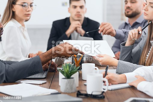 istock Manager passing documents to his colleagues at meeting 1084111494