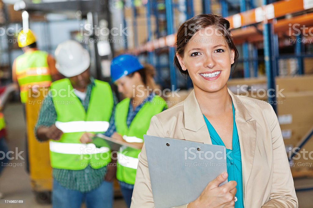 Manager posing in shipping/distribution warehouse with workers stock photo