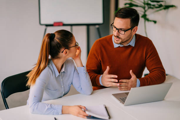 Manager providing direction to his team member stock photo