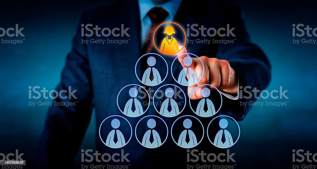 Manager Selecting A Female Worker Atop A Pyramid stock photo