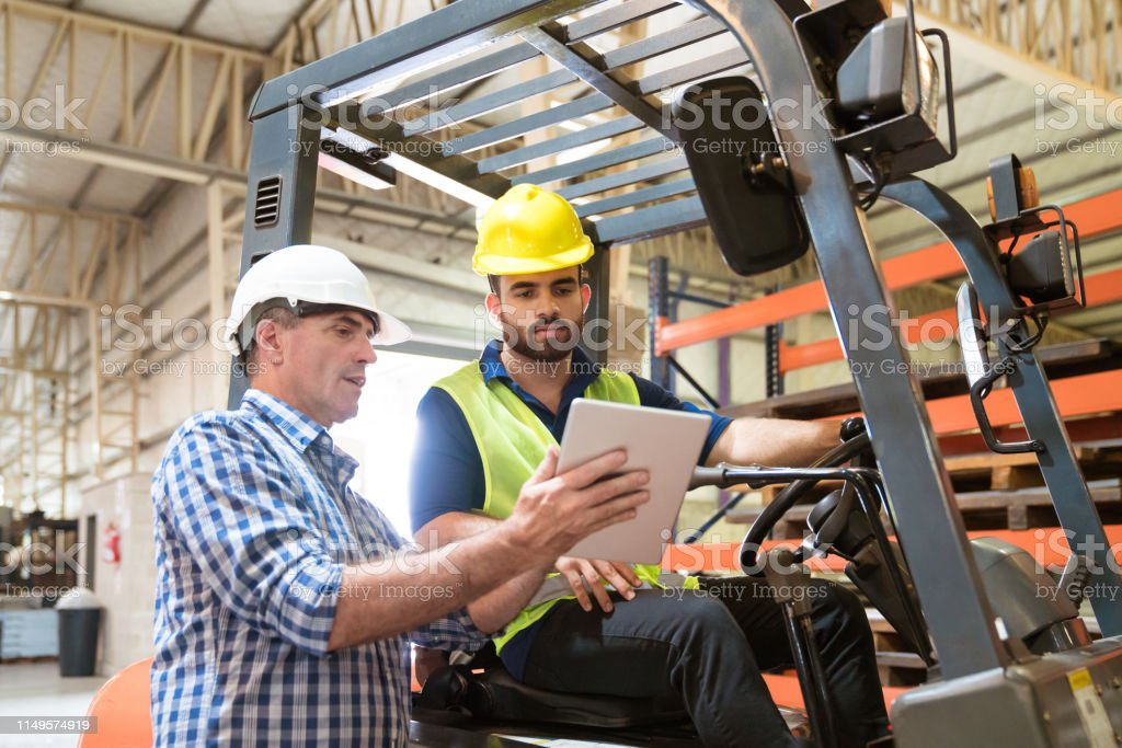 Manager showing digital tablet to manual worker Mature manager showing digital tablet to colleague in industry. Production worker is sitting on forklift. They are working together. 20-24 Years Stock Photo