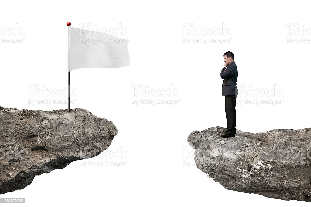 Manager standing on cliff with blank flag and white stock photo