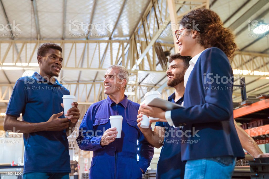 Manager taking break with engineers in warehouse Smiling colleagues looking at worker while having coffee. Manager is taking break with engineers in warehouse. They are in factory. 20-24 Years Stock Photo