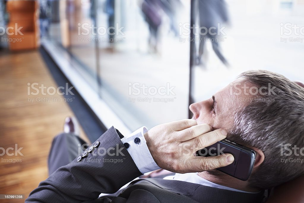 Manager talking on phone with busy people in background. royalty-free stock photo