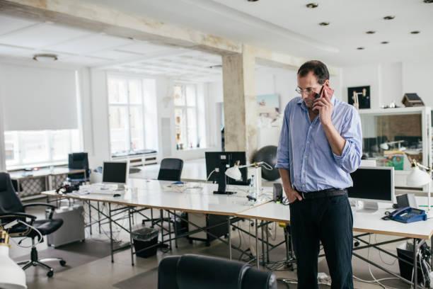 Manager auf Smartphone In leeren Büroflächen im Gespräch – Foto