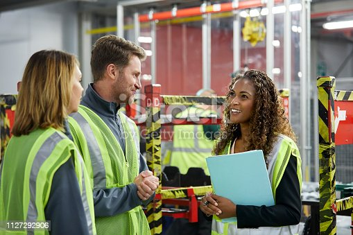 istock Manager talking to engineers in car plant 1127292906