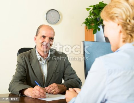 584597964 istock photo manager talking with a pensioner 512360309