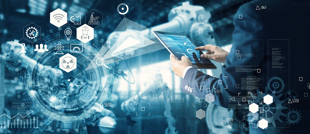 Manager Technician Industrial Engineer working and control robotics with monitoring system software and icon industry network connection on tablet. AI, Artificial Intelligence, Automation robot arm machine in smart factory on blue digital background, Innovative and futuristic technology.