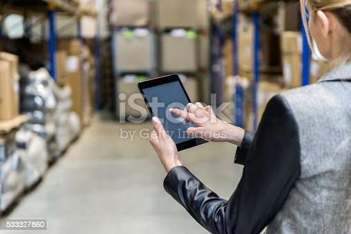 Horizontal color image of businesswoman - unrecognizable person - touching a digital tablet with blank screen in large futuristic storage compartment. Woman standing in aisle of distribution warehouse with touchscreen tablet in hand. Focus on businesswoman's hand holding black tablet, futuristic warehouse full of packages for sending in background. Logistics, freight, shipping, receiving.