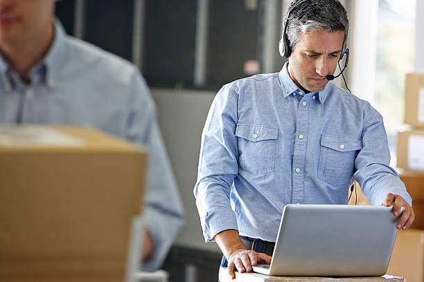 A manager using a headset and laptop stock photo