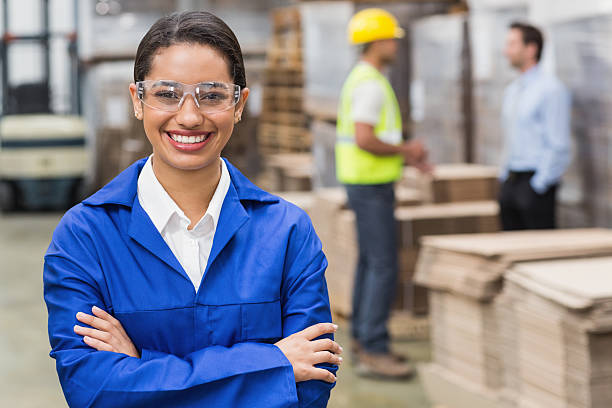 Manager wearing protective mask looking at camera Manager wearing protective mask looking at camera in a large warehouse protective eyewear stock pictures, royalty-free photos & images