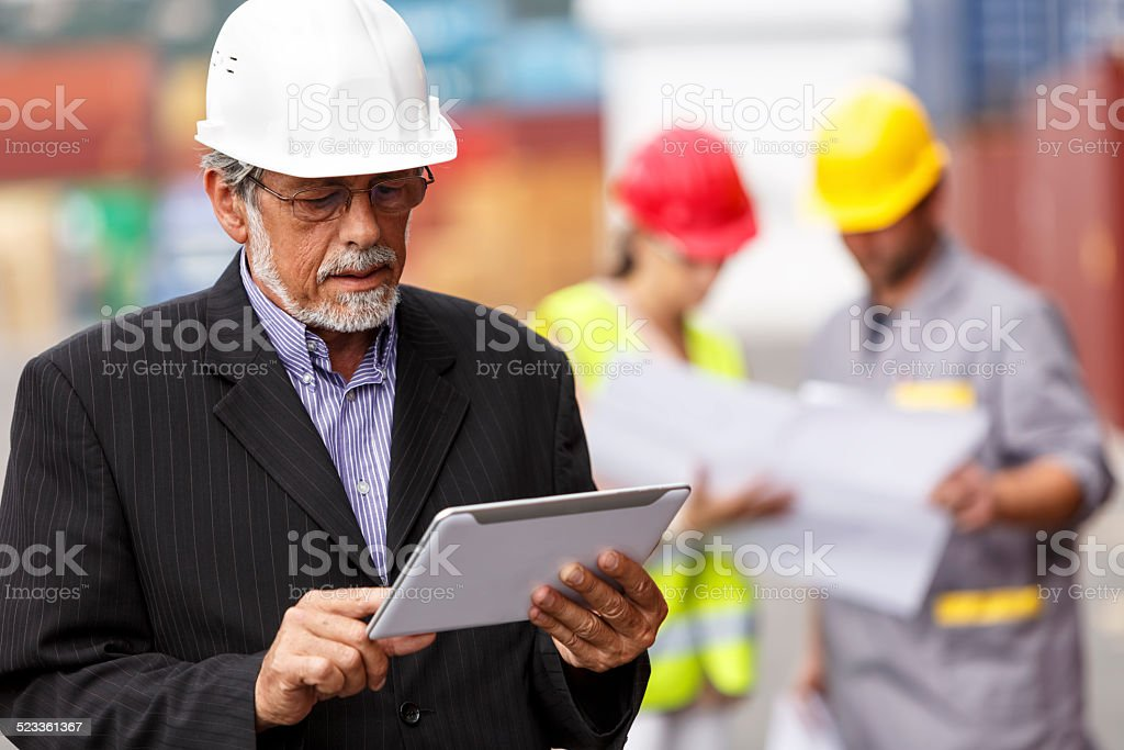 Manager with digital tablet at commercial dock stock photo