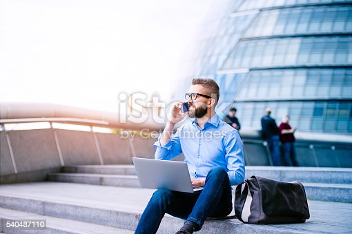 istock Manager with laptop and smart phone, London City Hall 540487110