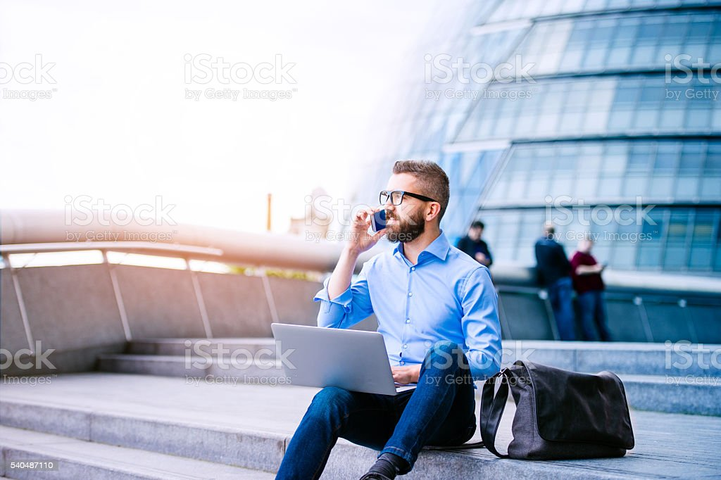 Manager with laptop and smart phone, London City Hall stock photo