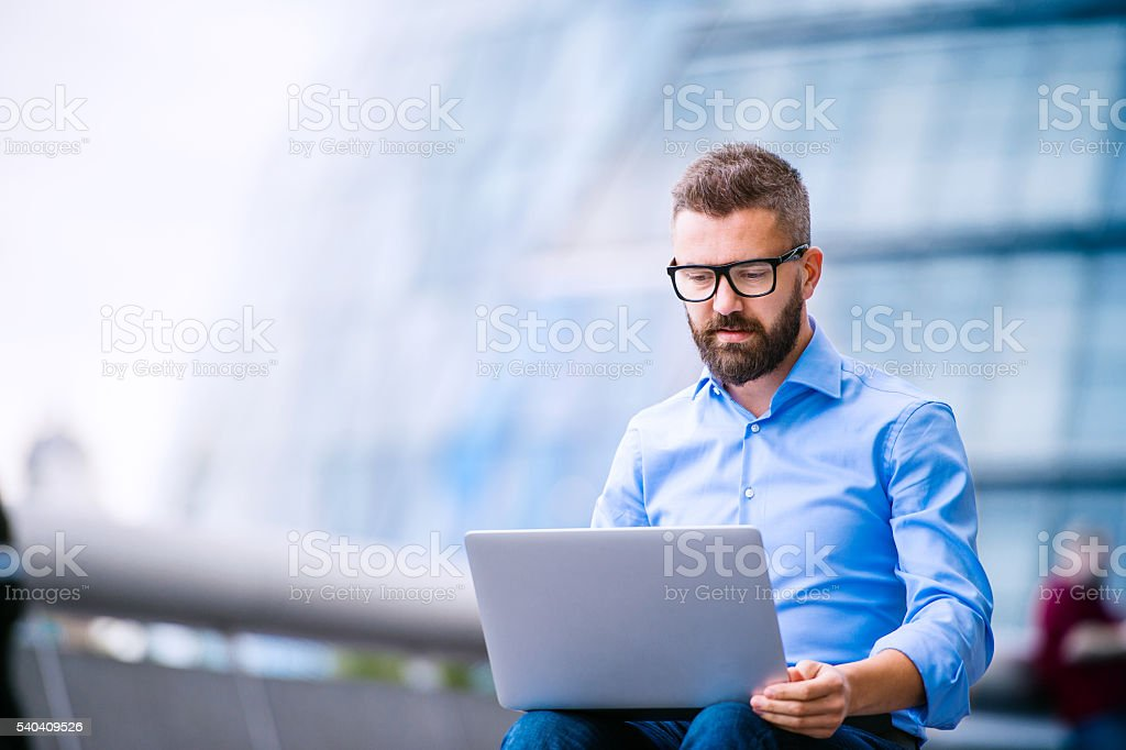Manager with laptop, sitting on stairs, London, City Hall royalty-free stock photo
