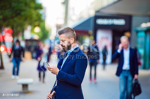 istock Manager with smartphone listening music outside in the street 512218152