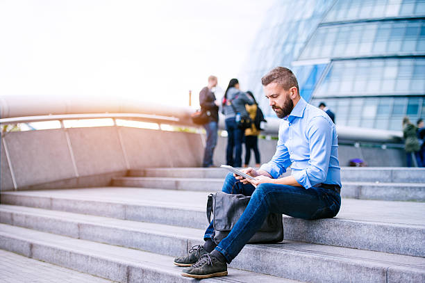 Manager with tablet, sitting on stairs, London, City Hall Hipster manager sitting on stairs on sunny day, working on tablet, London, City Hall local government building stock pictures, royalty-free photos & images