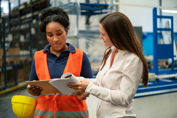 Manager with worker controlling stock in factory warehouse stock photo